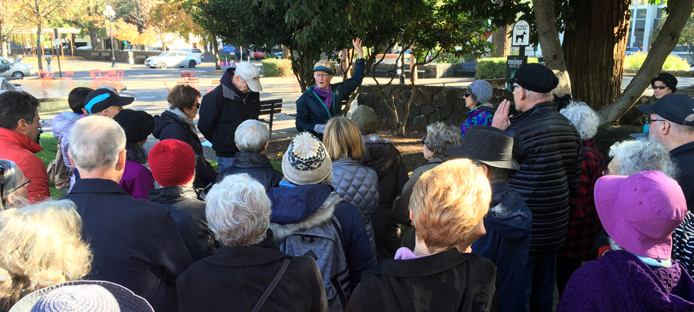Photo of group of OLLI-UO members listening to Tyler Burgess speak in downtown Eugene.